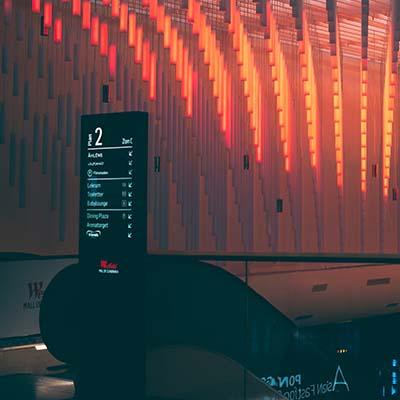 Borne d'information d'affichage dynamique au pied d'un escalator dans un batiment d'architecte