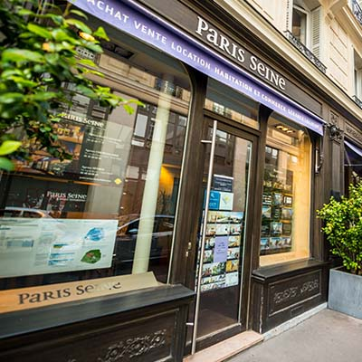 Écran d'affichage dynamique haute luminosité derrière la vitrine d'une agence immobilière avec mise en avant des plus belles offres
