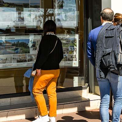 Écran d'affichage dynamique haute luminosité derrière la vitrine d'une agence immobilière avec mises à jour automatiques des annonces