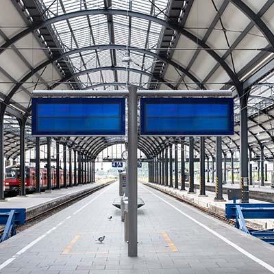 Écran d'affichage dynamique stretch sur un quai de gare avec prochains départ en temps réel