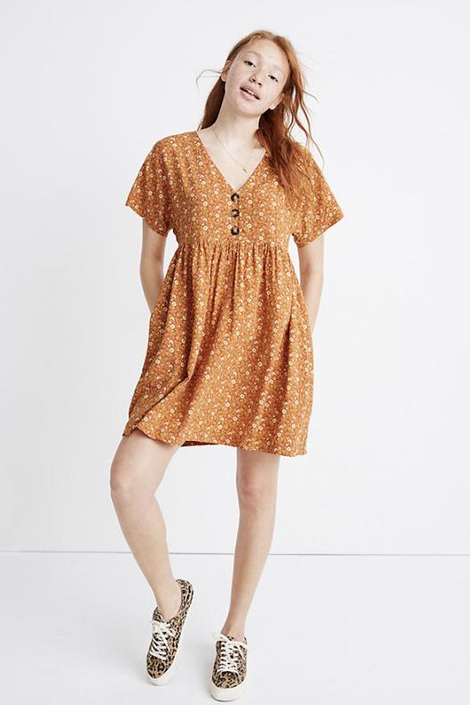 girl modeling short orange floral dress