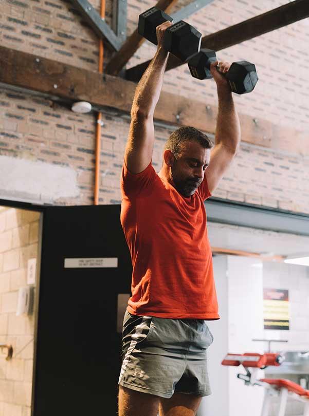 Male Camperdown Fitness member lifting dumbbells above head