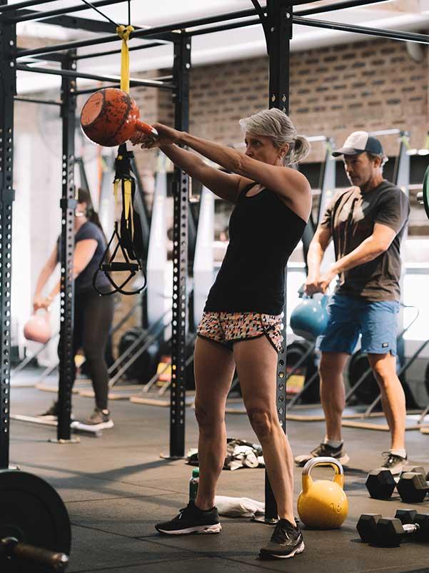 Female Camperdown Fitness member lifting kettlebell exercise