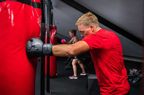 Man punching boxing bag in Camperdown Fitness boxfit class