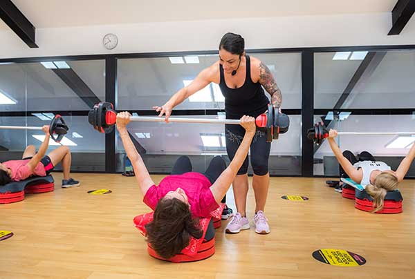 Woman lifting weight bar in Camperdown Fitness Body Pump class