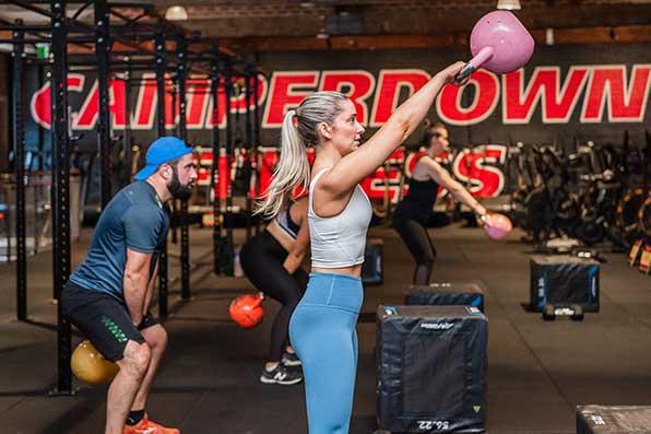 Woman raising pink kettlebell in Camperdown Fitness XFit Blast class