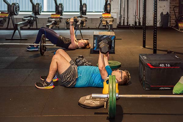 Camperdown Fitness gym member working out on floor with dumbbells