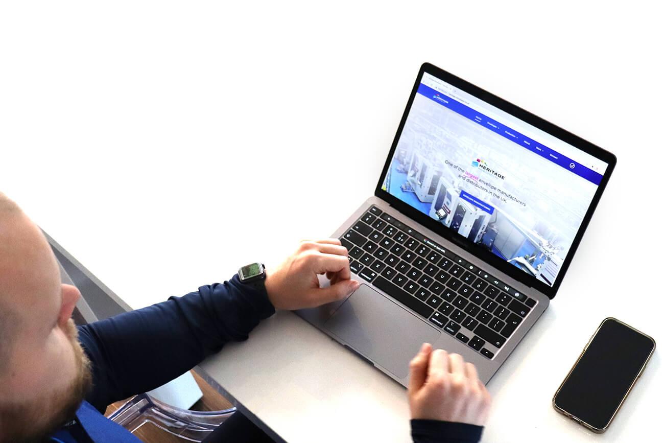 Steve designing a website on a laptop.