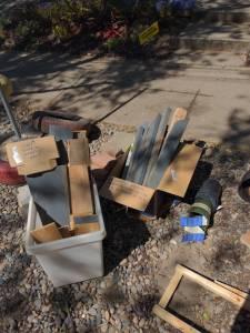 Wood and cedar scraps, plastic plant pots, brick