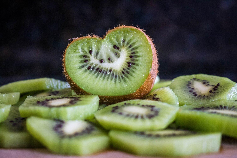A kiwi fruit in the shape of a heart, sliced open