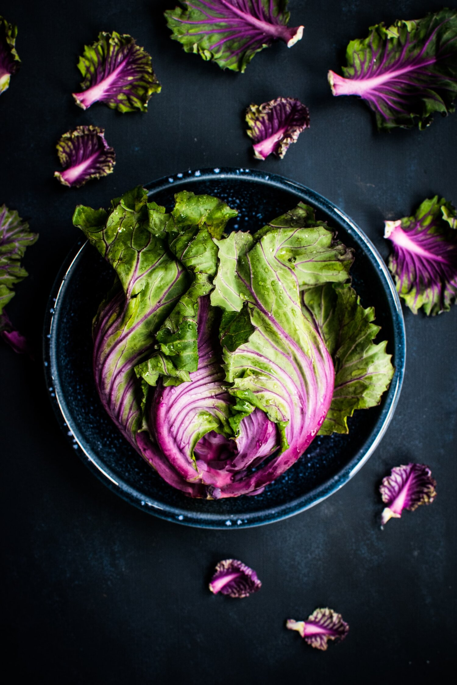 Purple lettuces resting in a green bowl