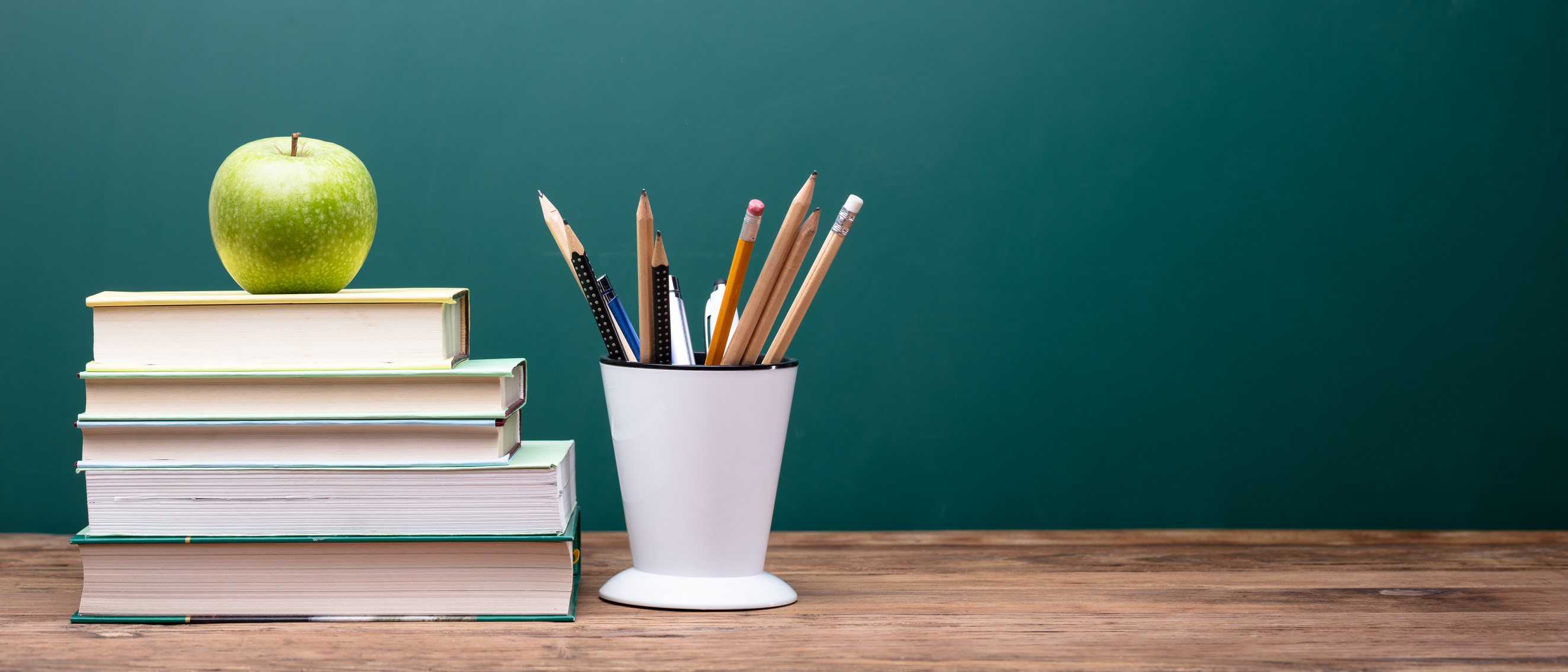 A stack of books with an apple and container with pens on a desk
