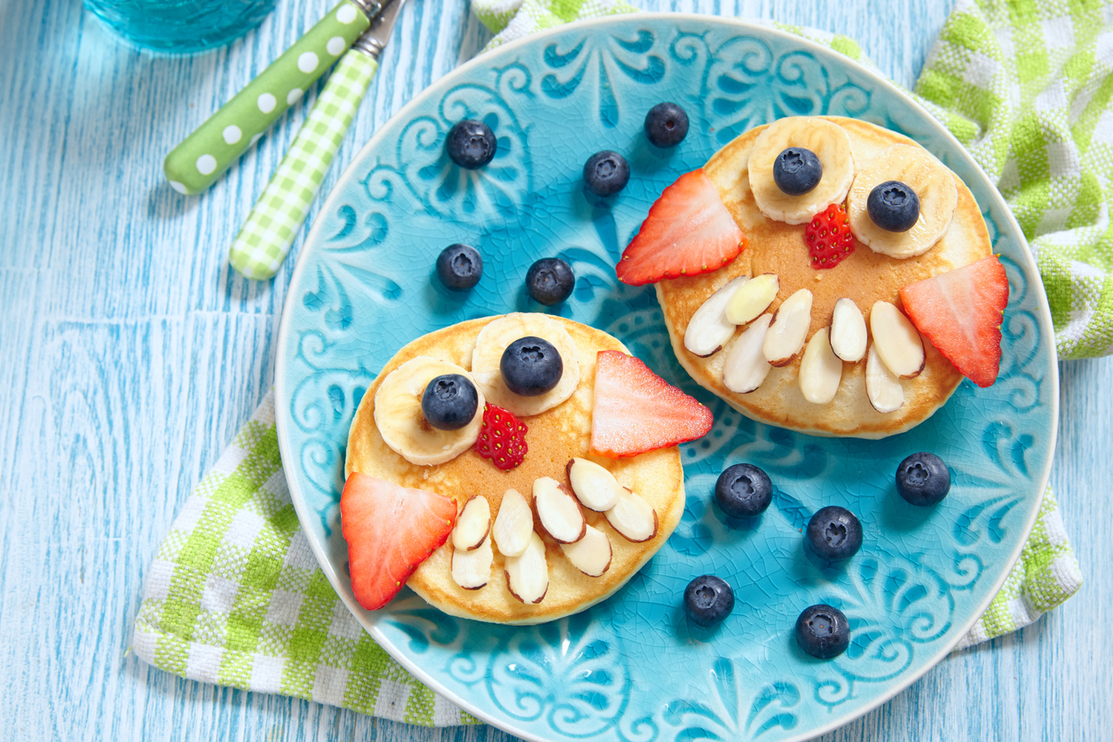 Pancakes made into an owl with fruits and almonds