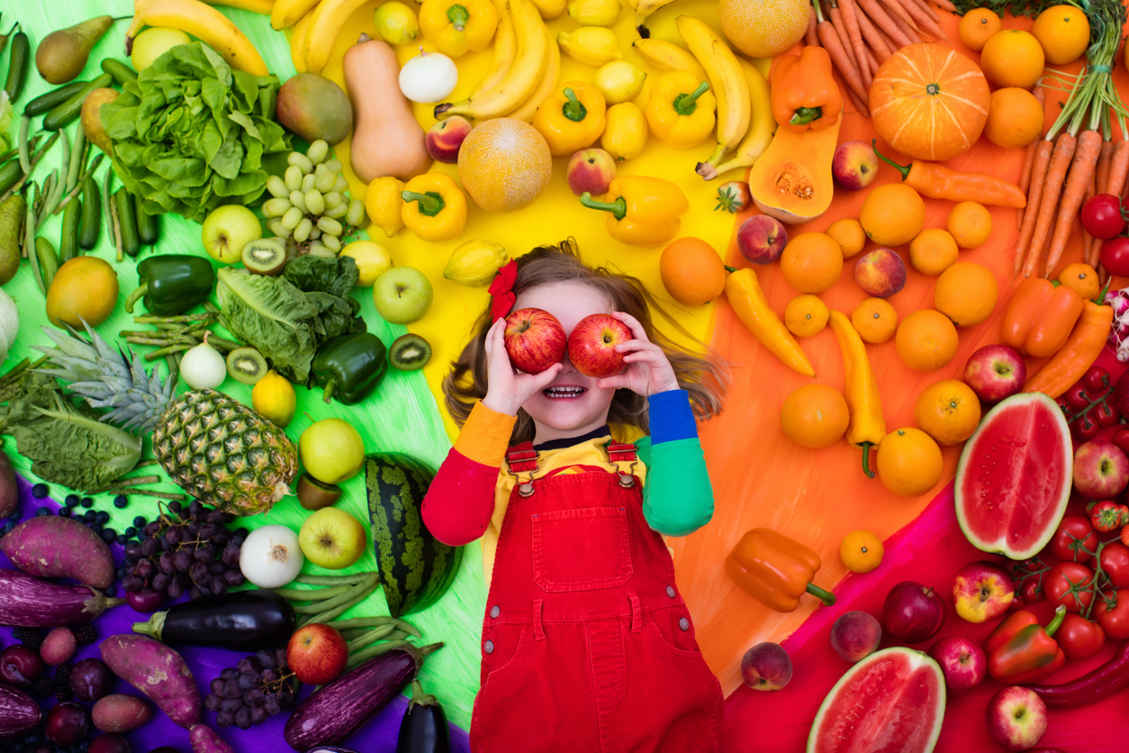 Happy child laying on a rainbow of fruits and vegetables