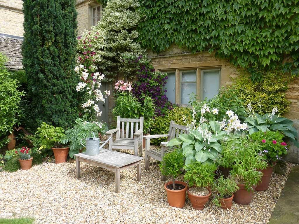 Wooden garden chairs surround by flowers