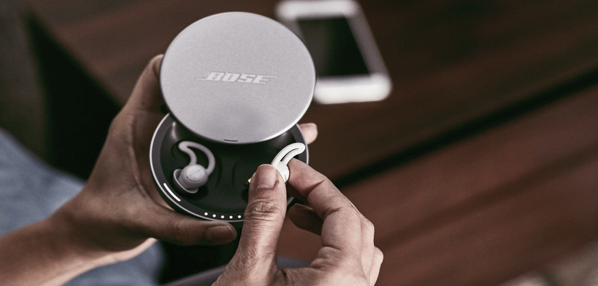 Close-up picture of hand holding Bose Sleepbuds with a phone in the background.