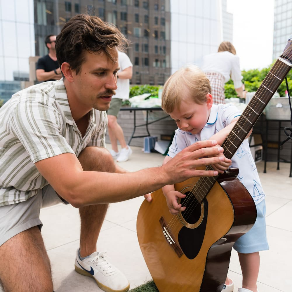 Teacher lets birthday boy hold guitar