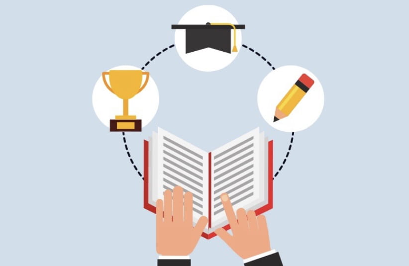 Hands in front of a book with a trophy, graduation cap, and a pencil above the book