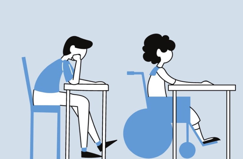 Girl in a wheelchair sitting at a desk