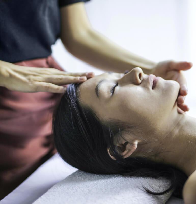 A relaxed woman receiving a head massage