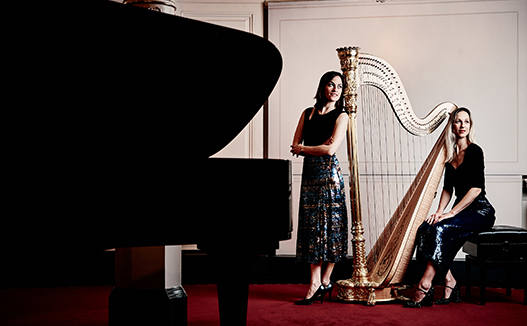 dorience sitting next to harp and other musician standing beside. Both are next to a grand piano on the left.