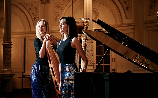 mid range shot of doriene marselje leaning on her harp and Celia Garcia leaning on grand piano in classical music room.
