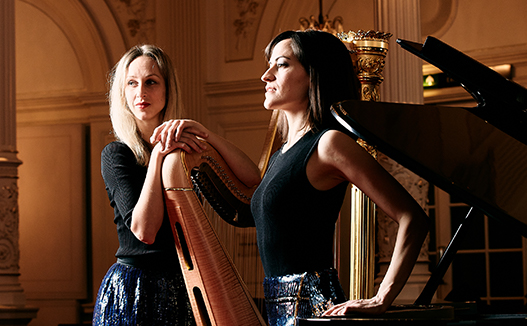 close up of doriene marselje leaning on her harp and Celia Garcia leaning on grand piano in classical music room.