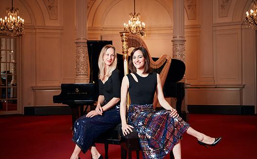 doriene marselje and Celia Garicia sitting in classical music room. Harp and grand piano in the background.