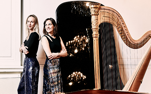 doriene marselje and Celia Garcia leaning on each other with harp and piano beside them in white room.
