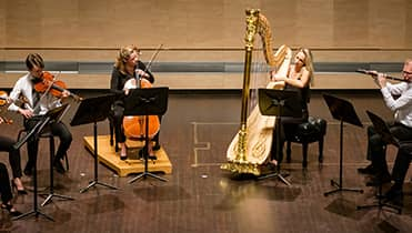 4 musicians playing onstage - left to right - violin cello harp and flute.