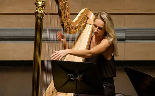 semi close up of doriene marselje playing the harp on stage with a striped background.