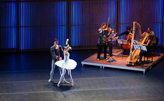 ballerina and man dancing on stage with 3 musician on a small stage. dark blue soft glowing lights in the background.