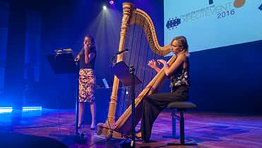 Doriene playing the harp with her sister on the blue and purple lit stage with white screen in the background.