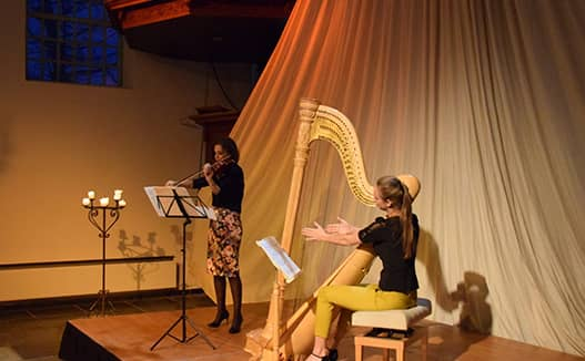 doriene marselje playing harp on the right with her sister to the left on a red and white lit stage