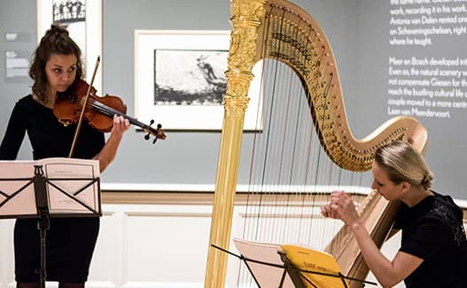 doriene marselje playing harp with her sister to the left in an art white art gallery