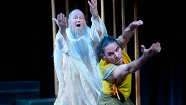 old man with long beard and white robe with a man in yellow and green outfit dancing in front.