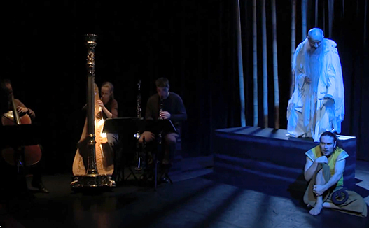 doriene marselje playing harp on the left with dimly lit spotlight. Old man in white robe performing on the right with blue colour light.