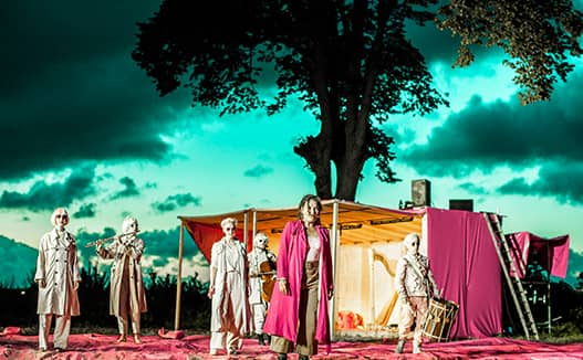 surreal green sky and pink foreground with performers dressed in white wigs and black glasses.