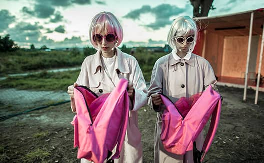 doriene marselje and musician in on the right holding pink bag. They are dressed in white wigs and black glasses.