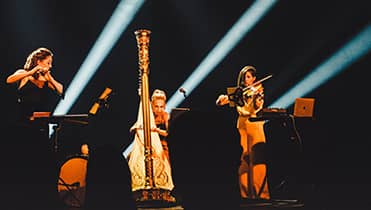 doriene playing harp with two other musicians playing violin on stage. spot light on all the musicians.
