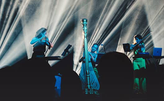 doriene playing harp with two other musicians playing violin on stage. The lights are shining up creating a blue light and a dar silhouette foreground.