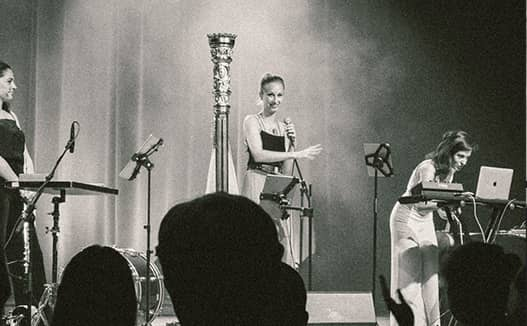 black and white image of doriene on stage with musicians. Audience silhouette heads in the foreground.