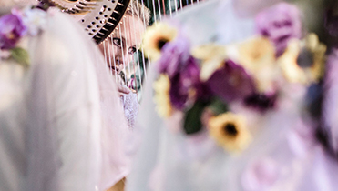 close up of Doriene Marselje's face with blurred floral white dress in the foreground.