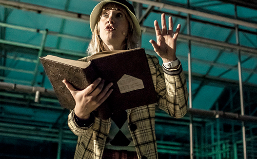 close up of person reading from an old book. Green warehouse background.
