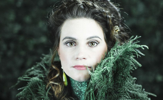 close of main performer waering a green feather outfite. She is brunette and fair skin with a a neutral smile.