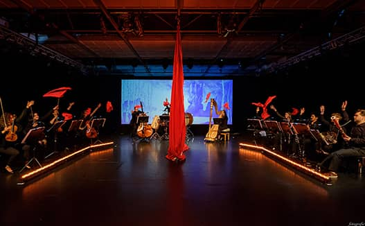 dimly lit stage with red curtain rope handing in the middle. Musicians on the right and left with projector screen at the back