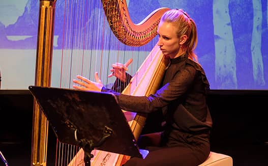 strong red purple light shining on doriene marselje playing harp in front of a projector screen.