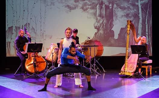 Man dancing in front of woman on stage while 3 musicians in the back. Doriene Marselje on the right with video screen in the background.