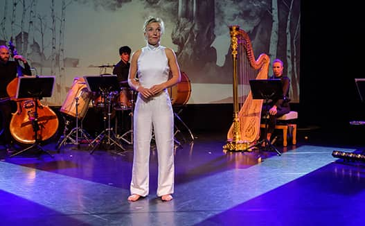 woman standing center stage with the musicians playing behind her. Project screen with visuals on trees.