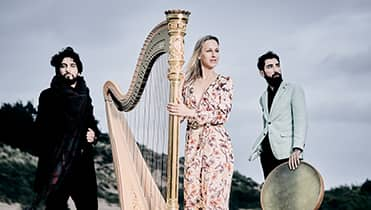 2 musician with doriene marselje in the middel next to harp. Two men on either side of her standing outside in front of hill.